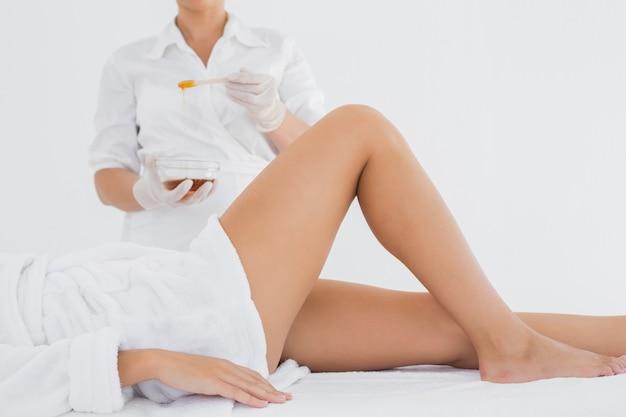Terapeuta depilando la pierna de la mujer en el centro de spa