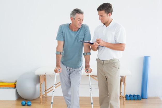 Terapeuta discutiendo informes con paciente discapacitado en gimnasio hospital