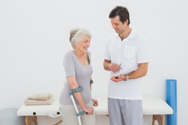 Terapeuta discutiendo informes con un paciente mayor con discapacidad