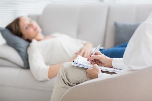 Terapeuta escribiendo notas del paciente