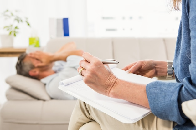Terapeuta escuchando paciente masculino y tomando notas