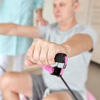 Terapeuta en fisioterapia con paciente masculino