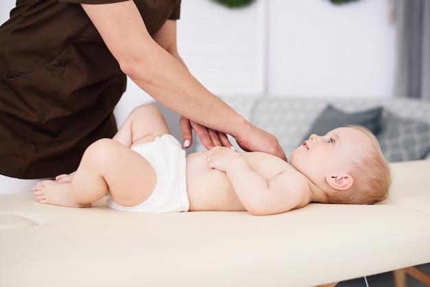 El terapeuta hace masajes a un bebé pequeño en una habitación moderna y acogedora. cuidado de la salud y concepto médico.