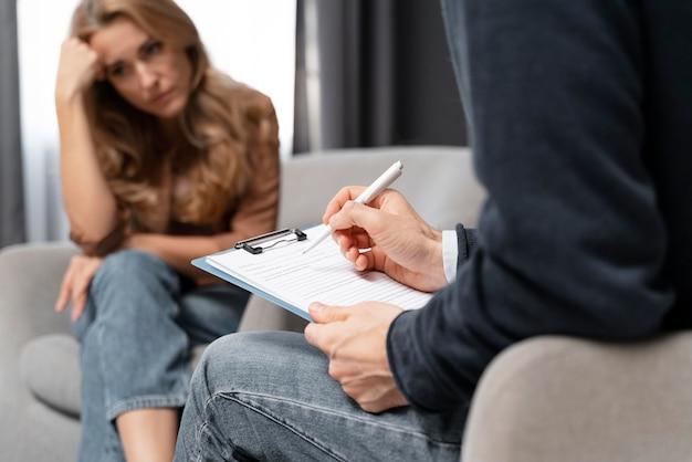 Terapeuta de hombre de tiro medio tomando notas cerca de la mujer