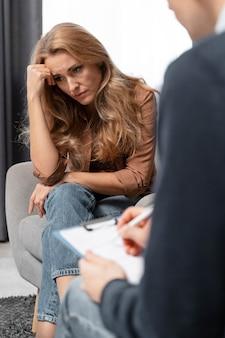 Terapeuta de hombre tomando notas junto a la mujer