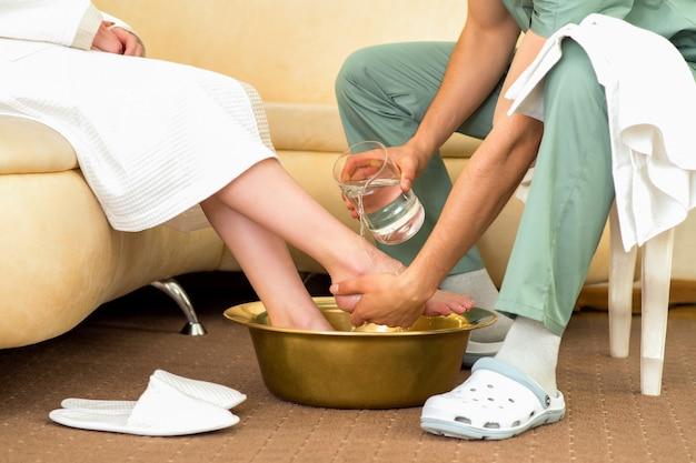 El terapeuta de masaje lava los pies de la mujer en el salón de masajes.