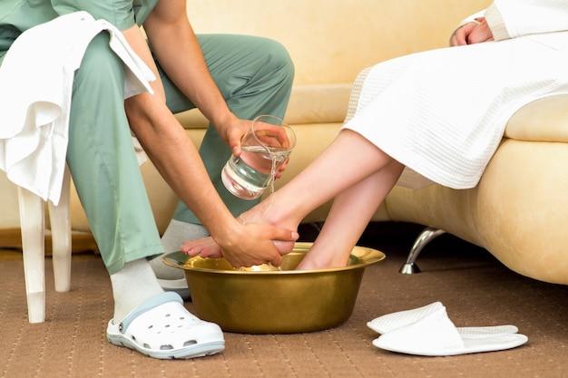 El terapeuta de masaje lava los pies de la mujer.