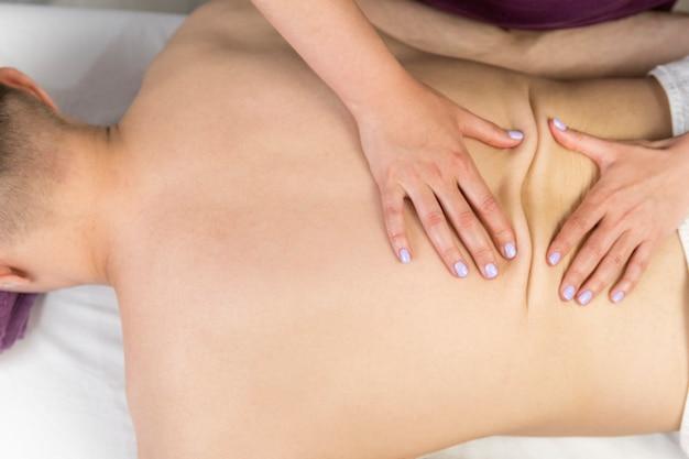 Terapeuta de masaje mujer da masaje a hombre joven. masaje profesional en la espalda en el salón de spa. procedimiento de bienestar