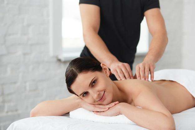 Terapeuta de masaje profesional está tratando a una paciente en el apartamento.