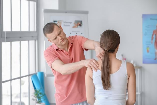 Terapeuta de masaje que trabaja con el paciente en el centro médico
