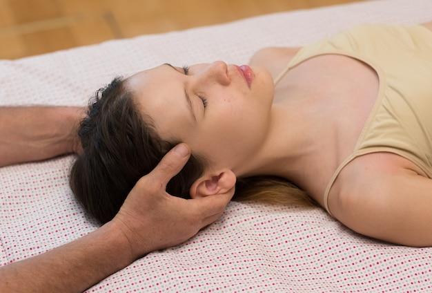 Terapeuta de masaje quiropráctico que trata a un paciente joven