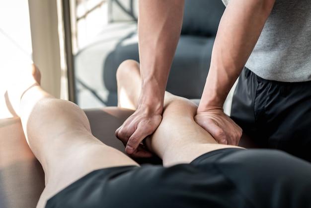 Terapeuta masculino dando masaje de piernas y pantorrillas a paciente atleta