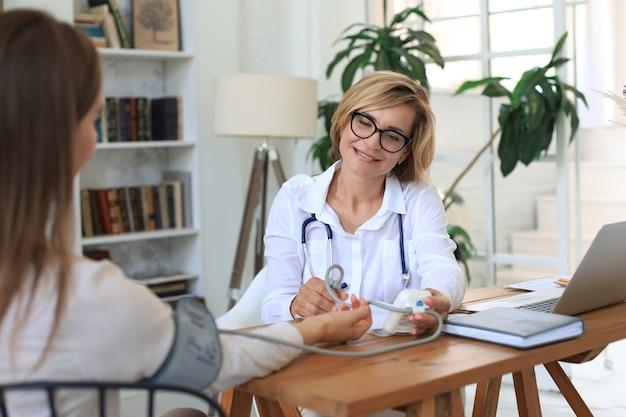El terapeuta mide la presión del paciente en consulta.