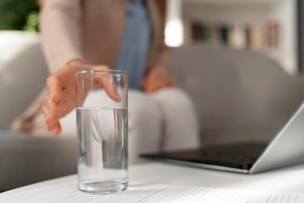 Terapeuta de mujer de primer plano alcanzando un vaso de agua