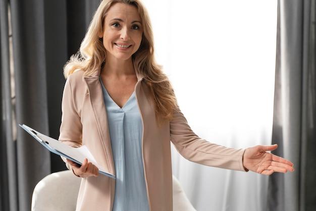 Terapeuta de mujer de tiro medio con portapapeles en el gabinete