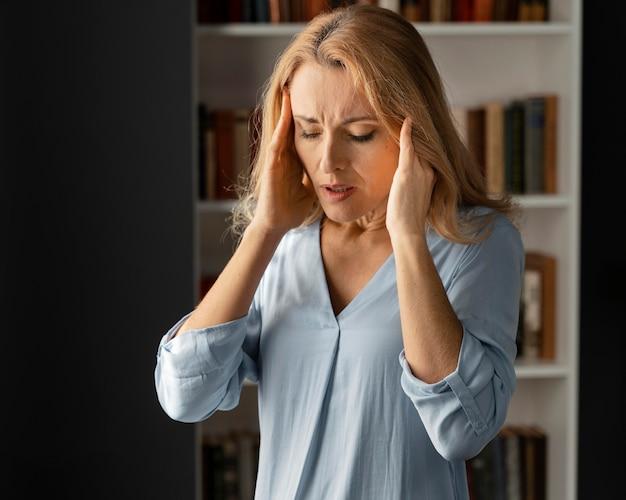 Terapeuta de mujer de tiro medio tomados de la mano en la cabeza