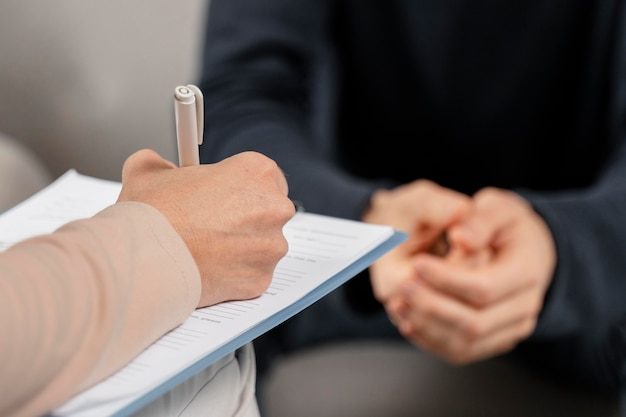 Terapeuta de mujer de tiro medio tomando notas en el portapapeles