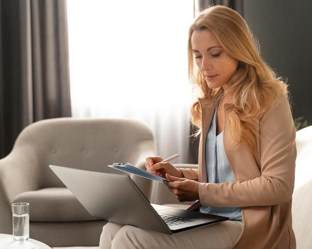 Terapeuta de mujer de tiro medio tomando notas con el portátil en el regazo