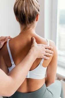 Terapeuta osteopático masculino comprobando la columna superior del paciente femenino
