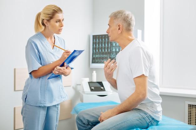Terapeuta personal. agradable anciano guapo sentado en el consultorio del médico y hablando con su terapeuta mientras se queja de su dolor