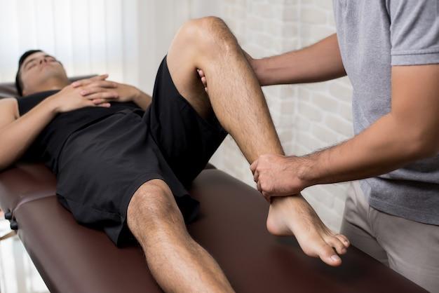 Terapeuta que trata la pierna lesionada del paciente masculino atleta en clínica