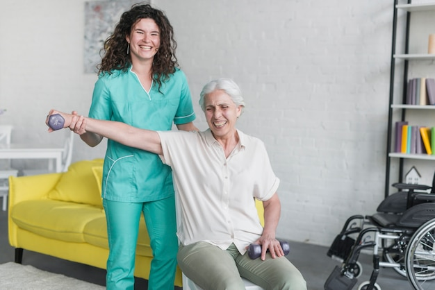 Terapeuta de sexo femenino que ayuda a la mujer mayor sonriente con pesas de gimnasia