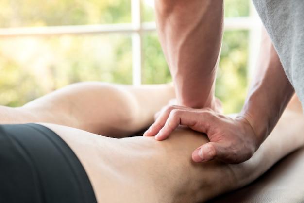 Terapeuta de sexo masculino que da masaje de la pierna al paciente del atleta en clínica
