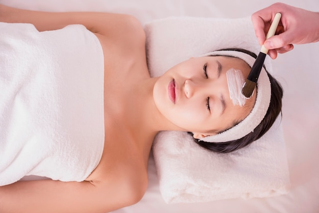 Terapia del balneario para la mujer asiática joven que recibe la máscara facial.