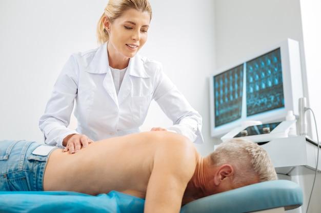 Terapia medica. doctora encantada profesional sonriendo y haciendo un masaje mientras trabaja con su paciente