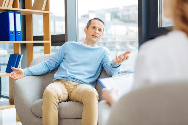 Terapia psicológica. hombre guapo agradable agradable sentado en el sillón y hablando con su médico mientras se somete a terapia psicológica