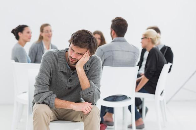 Terapia en sesión en círculo mientras el hombre en primer plano