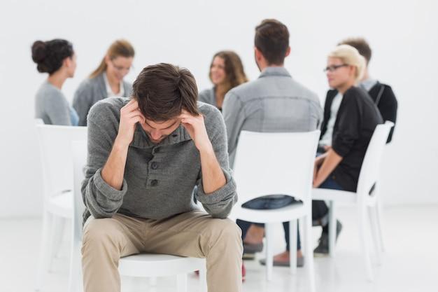 Terapia en sesión sentada en círculo mientras el hombre en primer plano