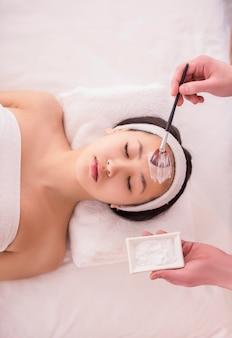 Terapia de spa para mujer asiática recibiendo máscara facial.