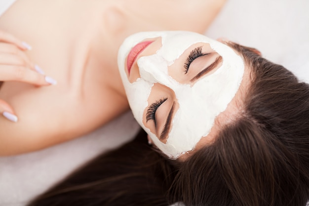 Terapia de spa para mujer que recibe mascarilla facial.