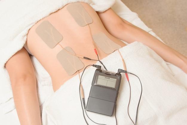 Terapia tens, electrodos de decenas en el músculo de la espalda
