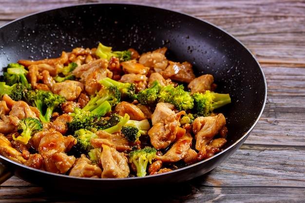 Teriyaki de pollo picante con brócoli en sartén sobre superficie rústica de madera