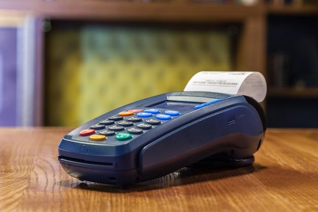 Terminal del banco con un cheque impreso y botones de colores sobre una mesa de madera. el concepto de pagar facturas en restaurantes y tiendas, comprar con tarjeta de crédito