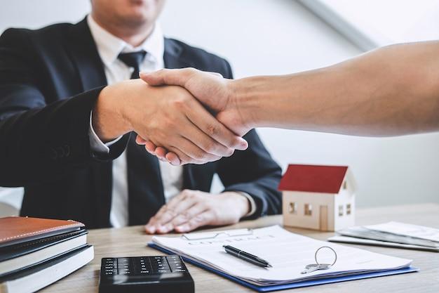 Terminando un acuerdo exitoso de bienes raíces, el corredor y el cliente se dan la mano después de firmar el formulario de solicitud aprobado del contrato, sobre la oferta de préstamo hipotecario y el seguro de la casa