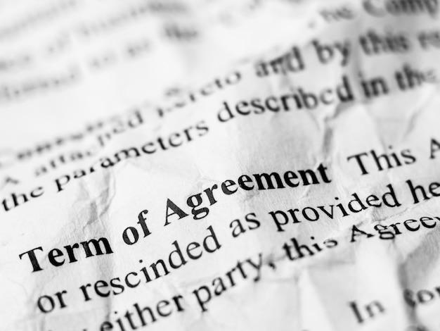 Término de mensaje de palabra de acuerdo en papel de contrato arrugado y arrugado