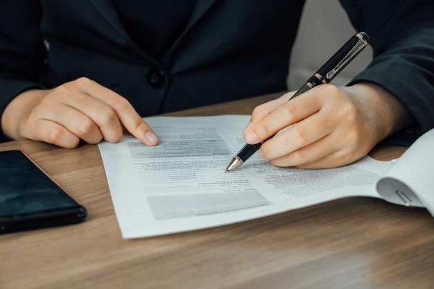 Términos de la firma de la empresaria y documento de la condición en la mesa de madera