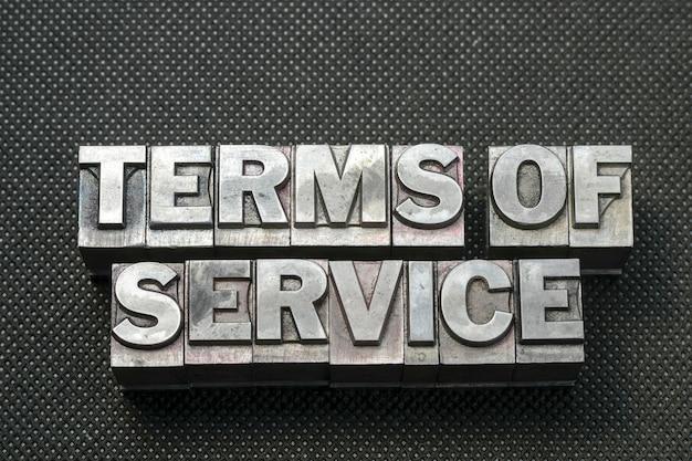 Términos de servicio frase hecha de bloques de tipografía metálicos sobre superficie perforada negra