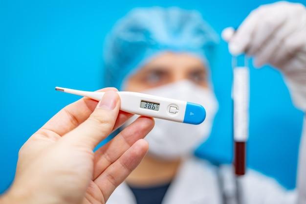 Termómetro electrónico en la mano y una joven doctora en una máscara con un tubo de ensayo con sangre en el que se encontró el coronavirus.