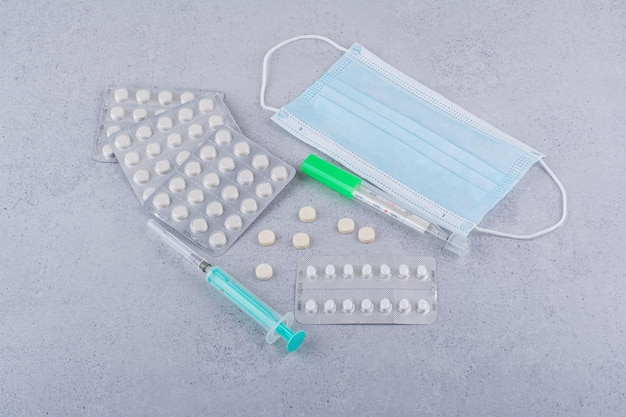 Termómetro, mascarilla, jeringa y píldoras médicas sobre fondo de mármol. foto de alta calidad