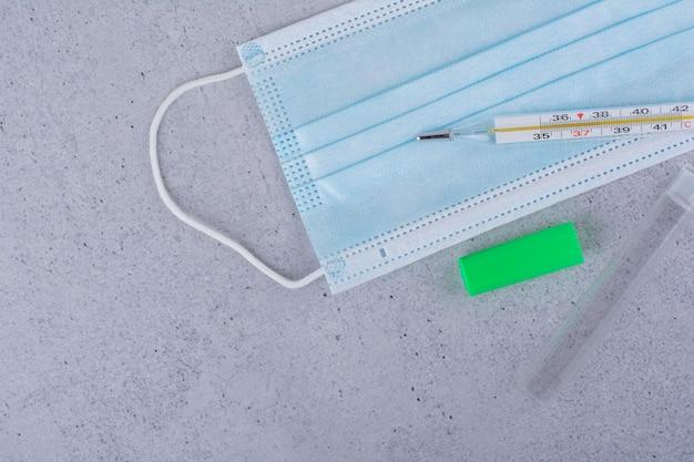 Termómetro y mascarilla de protección sobre fondo de mármol. foto de alta calidad
