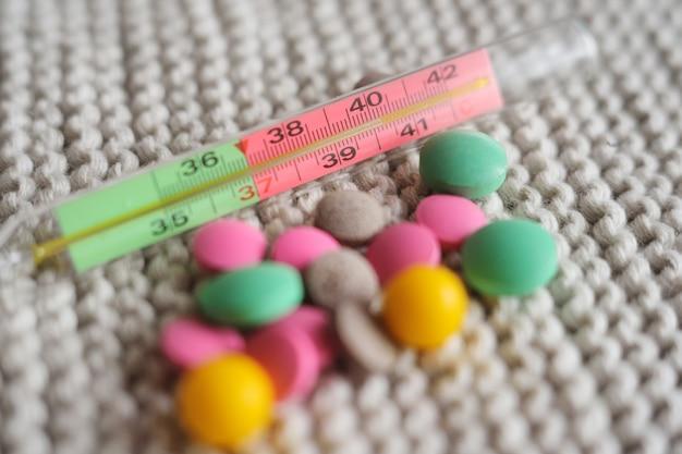 Termómetro y muchas tabletas de colores de primer plano sobre un fondo de punto