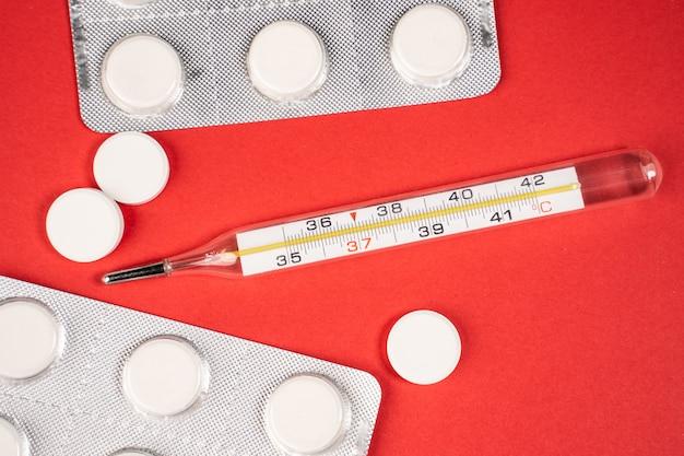 Termómetro y pastillas en mesa roja