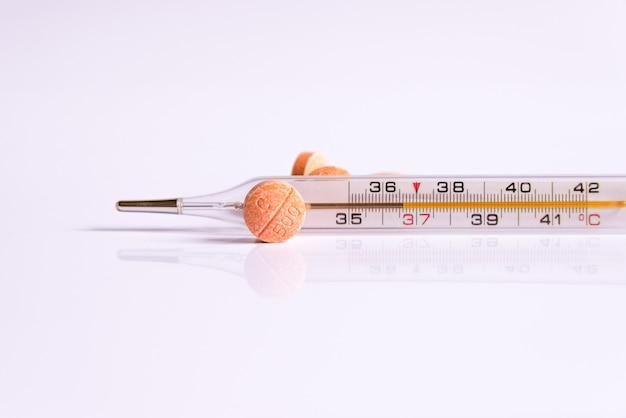 Un termómetro y vitaminas sobre un fondo blanco.