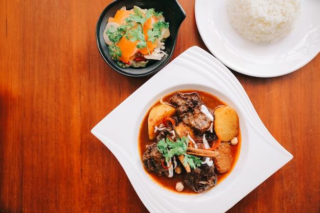 Ternera massaman curry con arroz y ensalada sobre fondo de madera, comida tailandesa