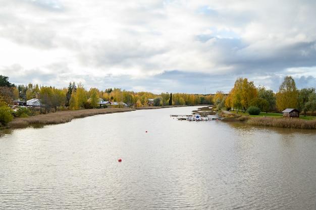 El terraplén de granito del río con casas de pueblo rojo