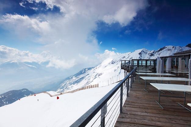Terraza en la cima de la montaña nevada y el paisaje del cielo nublado